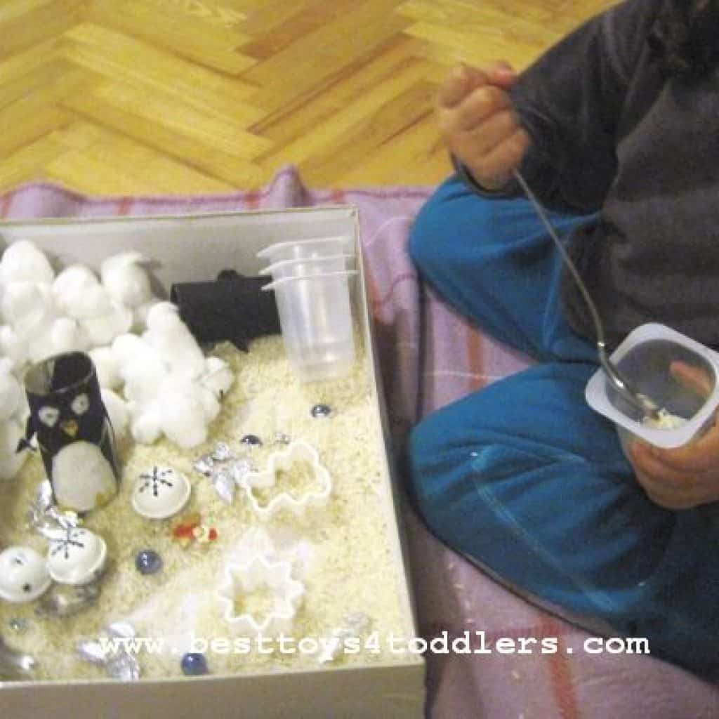 scouping and pouring with winter sensory bin