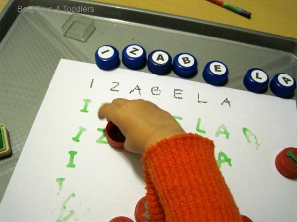 Printing using bottle caps as a way to practice name recognition with toddlers