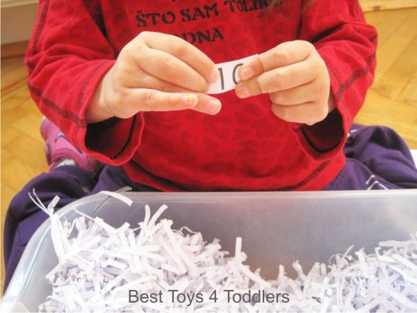 Hunting for numbers 1-10 as a part of sensory play with shredded paper