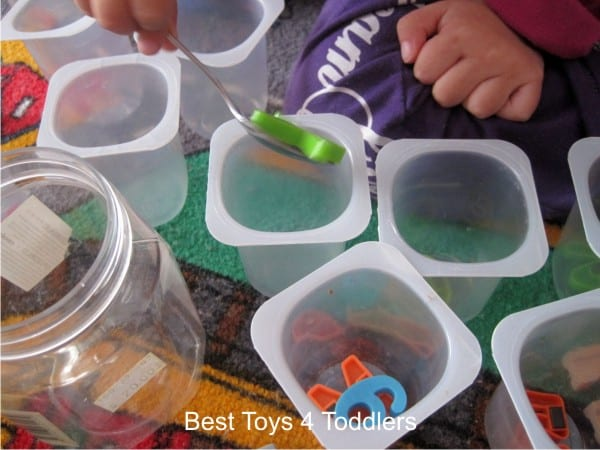 Practicing fine motor skills with todder using magnets, metal spoon and yogurt cups