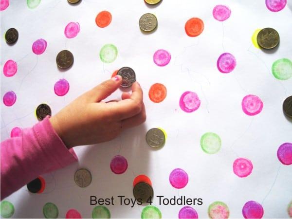 Working on fine motor skills with coins - placing coins over dots