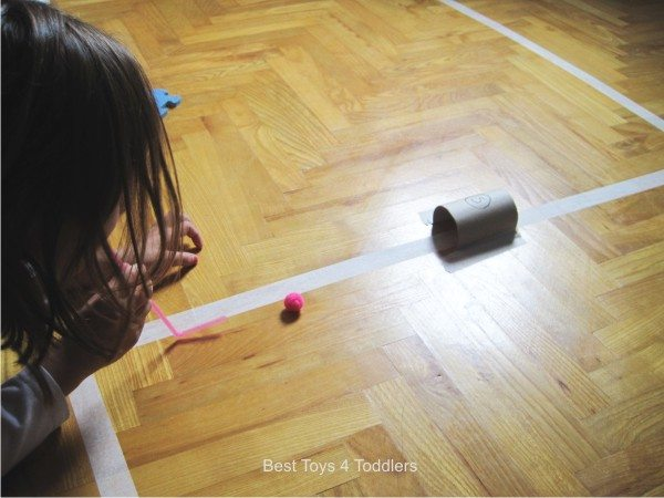 Racing pom poms through paper roll tunnels and keeping it on the path.