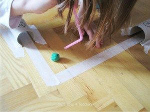 Having fun blowing pom poms through paper roll tunnels