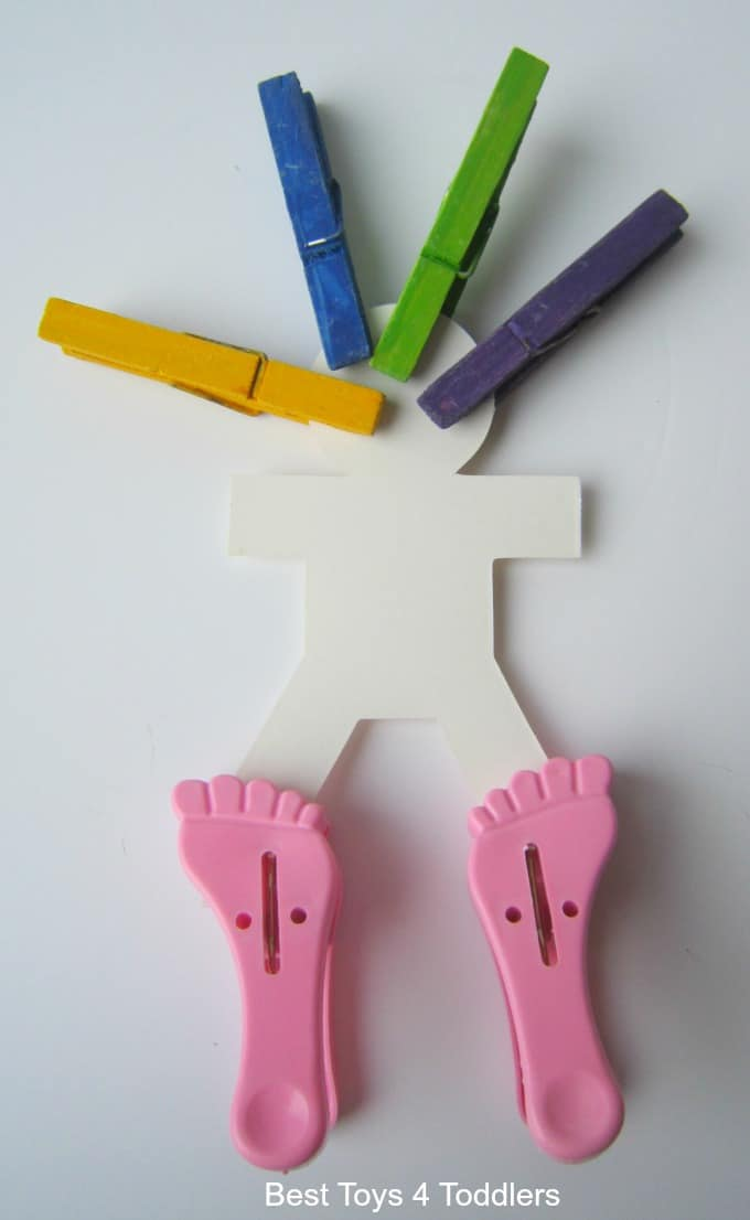 Decorating a paper chain boy with pegs