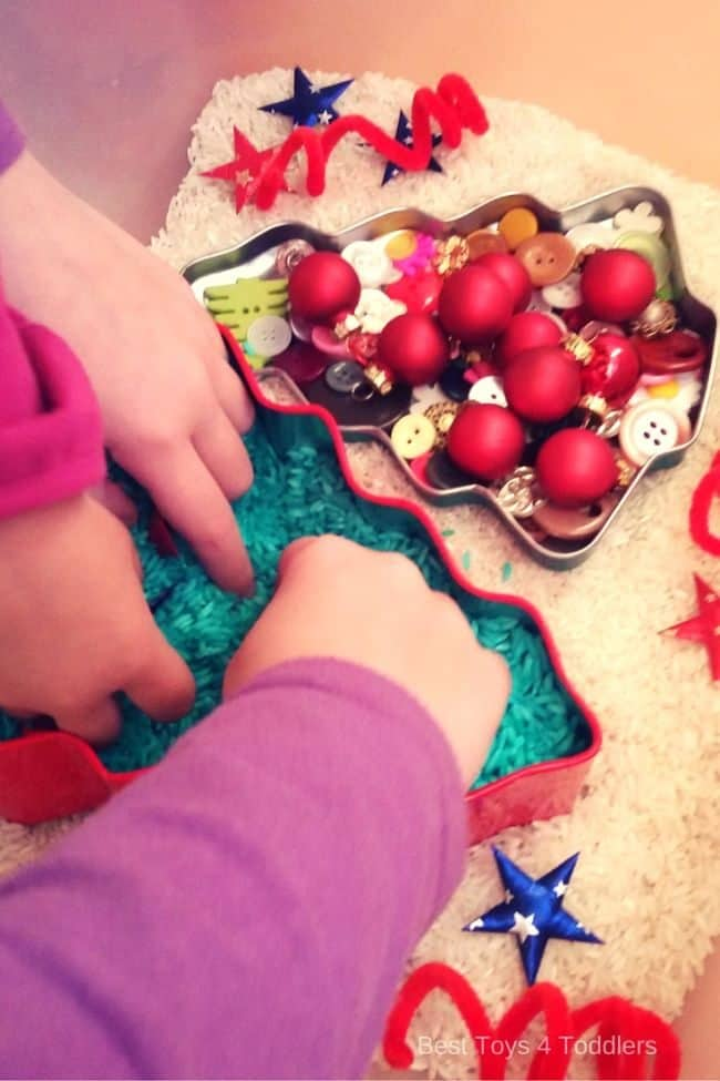 searching for burried ornaments and jingle bells inside mini Christmas tree created from green rice
